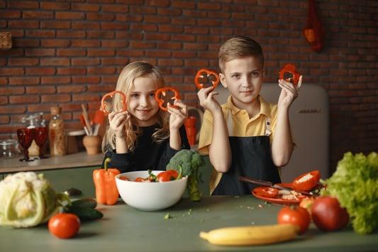 children-in-the-kitchen-holding-slices-of-capsicum-3984735